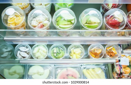 Cut apples in containers stored in fridge.Fresh fruits in slices packed in plastic transparent boxes in food store.Buy natural organic food in supermarket