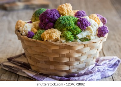Cut assorted cauliflowers of different colors in a basket on wooden background