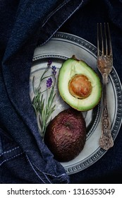 cut avocado fruit with lavender on a patinated, old plate