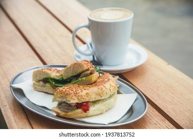 Cut Bagel And Coffee On Wooden Table From Cafe
