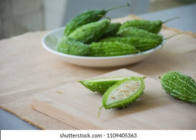Cut of bitter melon or bitter gourd on wooden plate with bitter gourd on white dish blurred background
