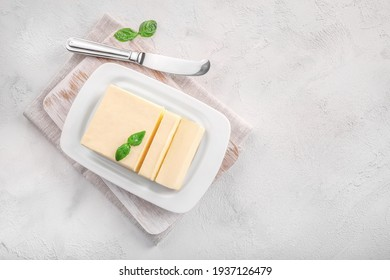 Cut block of fresh butter in white ceramic butter dish on white background. Top view. Copy space.