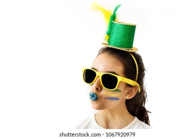 Cut Brazilian girl with sunglasses and hat doing funny face over white background. Soccer fan cheers. Green and yellow clothes and flag.