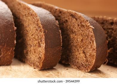 Cut bread (ciabatta) close-up on wooden board.