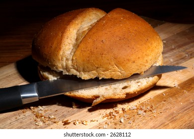 Cut bread roll with knife on a wooden board