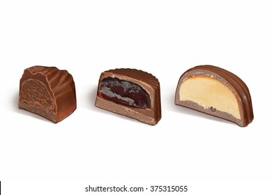 cut chocolate candies with different fillings on white background