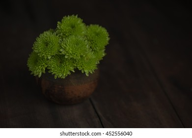Cut Chrysanthemum Flowers in Clay Pot on Vintage Wood Table