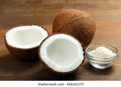 cut coconut with coconut flakes in glass bowl on brown wooden background