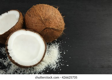 cut coconut with coconut flakes on black wooden background