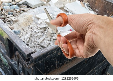 Cut construction waste concept with hand holding pair of scissors against construction dump