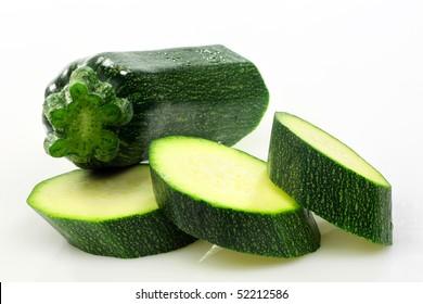 cut courgette or zucchini (Cucurbita pepo) on a white background