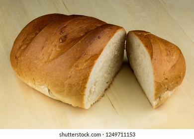 Cut crusty bread on a wooden bread board