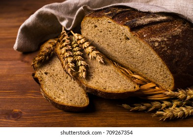 Cut dark bread on a wooden background with rye ears. Selective focus.