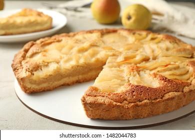 Cut delicious sweet pear tart on table, closeup
