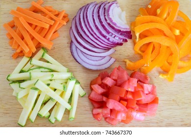 Cut and diced vegetables on a wooden cutting board. Onion, tomato, paprika, zucchini, carrot. Step by step cooking