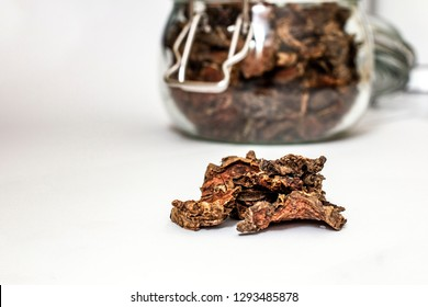 cut dry root of Rhodiola rosea in a glass jar on natural white background