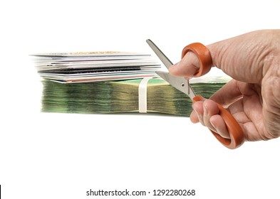 Cut expenses concept with hand holding pair of scissors facing credit cards and banknotes on white background