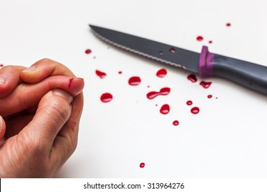 A cut of finger while cooking. Hand, knife and drops of blood on a white surface