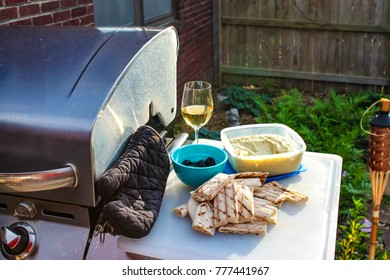 cut up flat bread and dip and olives and a glass of white wine sitting on a cutting board beside an outside gas grill with oven mit - tiki candle grass and wood fence in background