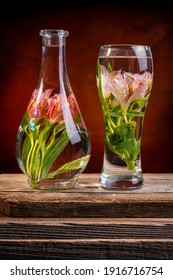 Cut flowers and pink lilies in a vase filled with water on a barn wood table in front of a dark canvas background
