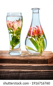 Cut flowers and pink lilies in a vase filled with water on a barn wood table in front of a white background