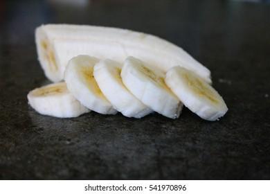 Cut up fresh banana in a dark background