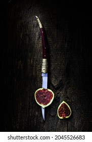cut fresh figs on a wooden table close-up next to a knife. sliced fresh figs macro