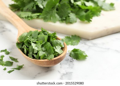 Cut fresh green cilantro and wooden spoon on white marble table, closeup. Space for text