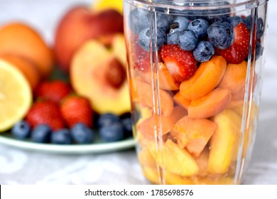Cut fresh summer fruit in layers in a mixing bowl, ingredients for a healthy smoothie