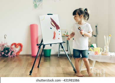 Cut girl painting in at her  home. Selective focus and small depth of field.