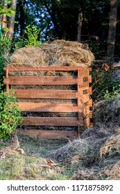 cut grass in a homemade wooden composter - zero waste in the garden