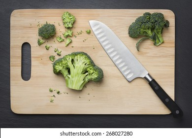 Cut green broccoli on wooden cutting board and knife.