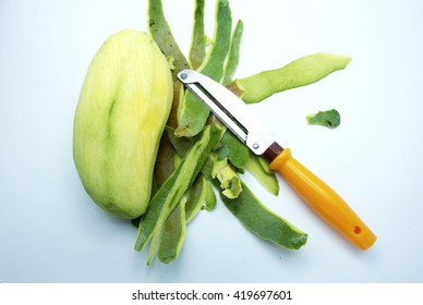 Cut green mango with skins and special kitchen knife on gray background.