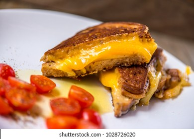 Cut up grilled cheese sandwich on a white plate with tomatoes