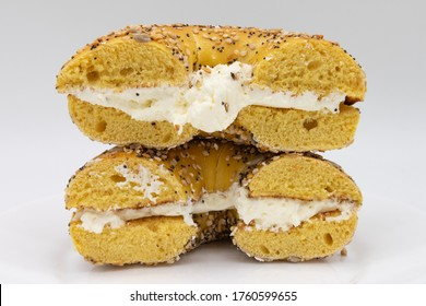 Cut in Half Egg Everything Bagel with Cream Cheese and a White Background