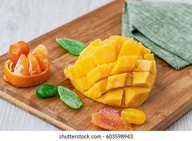 cut half a mango candied fruit, lying on a wooden Board