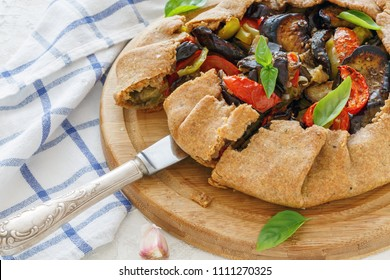 Cut homemade galette with tomatoes, eggplant and pepper on wooden serving board.
