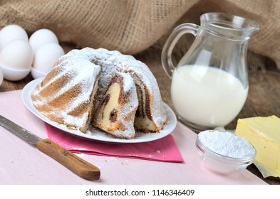 Cut of homemade marble cake sprinkled with sugar, lemon, melissa, milk, eggs and butter