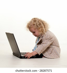 Cut little curly hair blond boy toddler in business suit sitting on floor typing on laptop computer over white