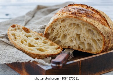 Cut loaf of artisanal wheat bread in a wooden box on a white table, selective focus.