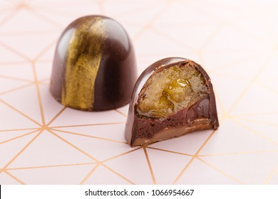 Cut luxury handmade candy with chocolate ganache and citrus fruit jelly filling on pink background. Exclusive handcrafted bonbon. Product concept for chocolatier