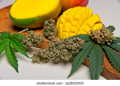 Cut mango fruit with cannabis leaves and buds. Myrcene and terpenes in mangos support effects of THC in cannabis. On wooden cutting plate on white background.