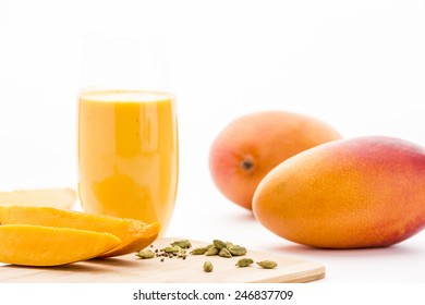 Cut mango fruit pieces and crushed cardamon on a bamboo cutting board. Key ingredients for the homemade mango yoghurt drink served in a plain drinking glass. Two whole mangoes. White background.