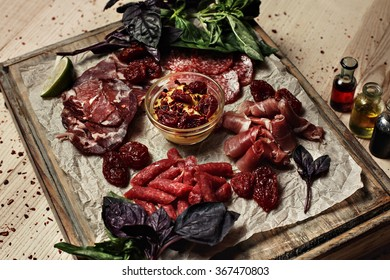 cut meat on wooden board decorated with basil