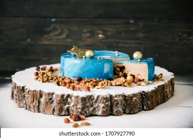 cut mousse chocolate cake with nuts space view on a wooden slice on a black wood background