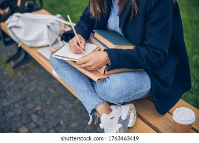 Cut off photo of female in casual clothes sitting on bench with legs while writing in notebook
