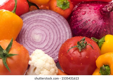 Cut onion and Vegetable Medley for salad with peppers, cauliflower, and tomatoes on white background. Health concept. Water Droplets.