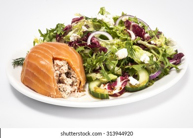 Cut open smoked salmon terrine with a mixed green salad isolated on white