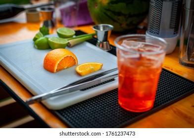 bei der Zubereitung des Cocktails Orange schneiden.
