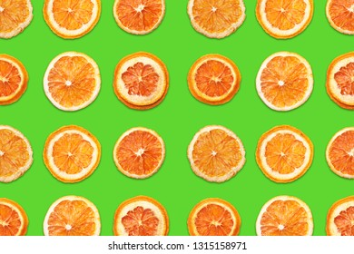 Cut orange fruit sections. Slices pattern design isolated on green background.